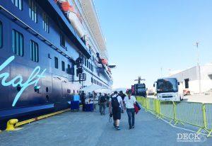 Busse für die Landausflugsfäste warten an der Pier, während die Gäste von der Mein Schiff zum Bus und zurück gehen.