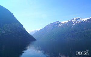 Aussicht aus dem Sightseeing-Boot auf den Geirangerfjord mit schneebedeckten Bergen