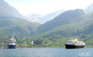 Mein Schiff 4 und die Astoria im Geriangerfjord vor der Kulisse von Geiranger.