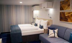 Innenkabine Mein Schiff 2: Bett vor gestreifter Wand, davor die Bettcouch