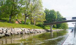 """Blick vom Boot auf die Parklandschaft und eine Brücke beim Mein Schiff Landausflug """"Stockholm auf zwei Arten erleben"""""""