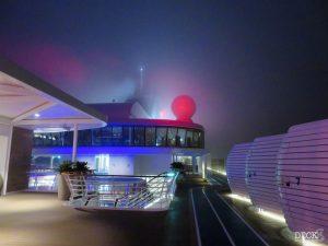Der Sportbereich der Mein Schiff 1 versinkt auf der Ostsee Reise mit St. Petersburg im Nebel. Blick vom Pooldeck bei Nacht.